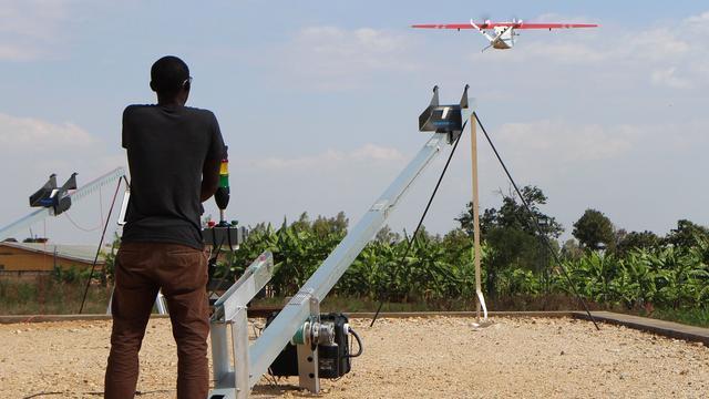 Een man lanceert een drone in Rwanda. Op deze foto uit 2016 gaat het nog om een proefvlucht. De drones kunnen bijvoorbeeld medicijnen of bloedmonsters vervoeren.