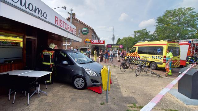 Auto knalt tegen gevel pizzeria in Van Nesstraat