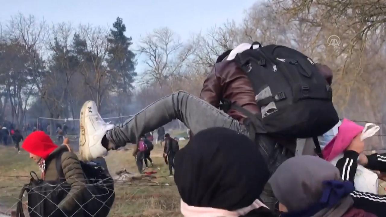 Syrische vluchtelingen klimmen over hekken bij grens met Europa