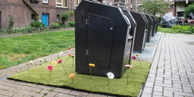 Gemeente plaatst kunstgras met bloemen bij afvalcontainers