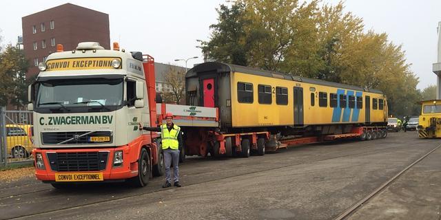 Oude treinstellen over de weg naar station Amsterdam Lelylaan