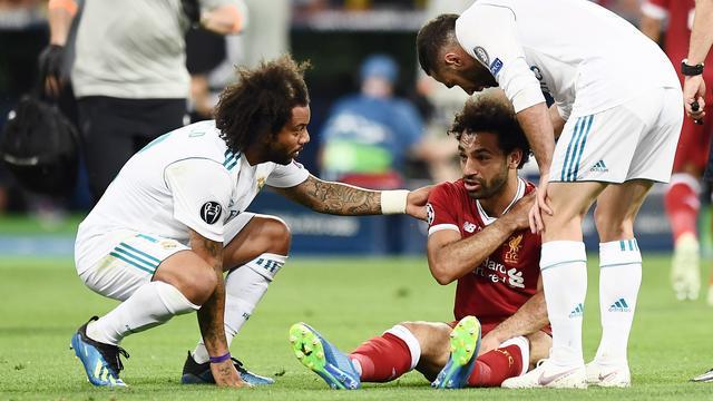 Mohamed Salah zit met een pijnlijke schouder op de grond na een overtreding van Sergio Ramos.