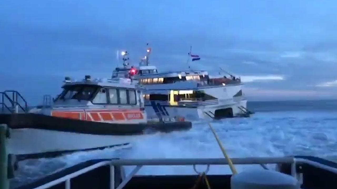 Sleepboten trekken vastgelopen veerboot los in Waddenzee