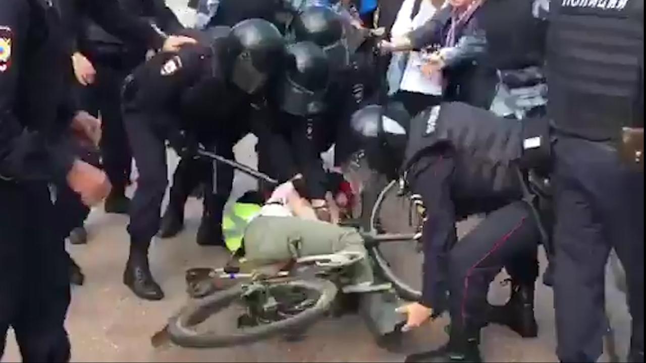 Politie sleept man op fiets richting wagen in Moskou