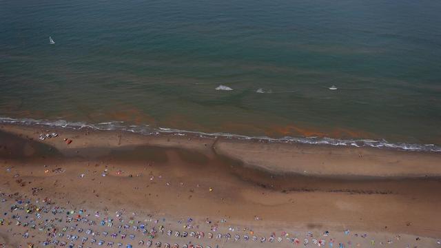 Rijkswaterstaat doet hele nacht onderzoek naar rode gloed in zee