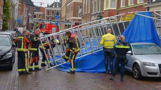 Bouwsteiger valt om op geparkeerde auto's bij Papengracht