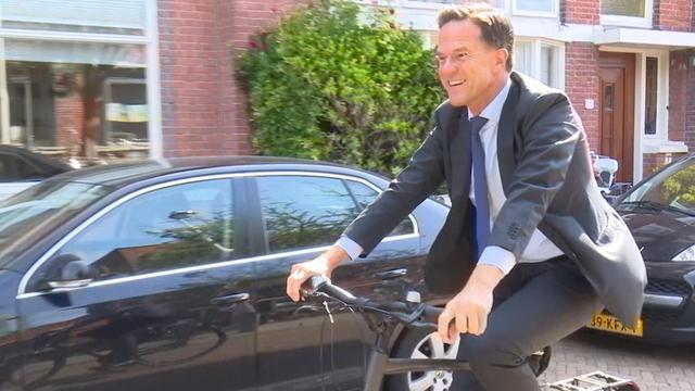 Rutte arriveert op de fiets bij zijn stemlokaal in Den Haag