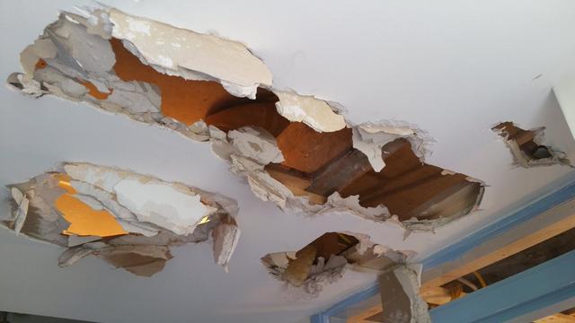 Brandweer haalt beknelde man uit plafond