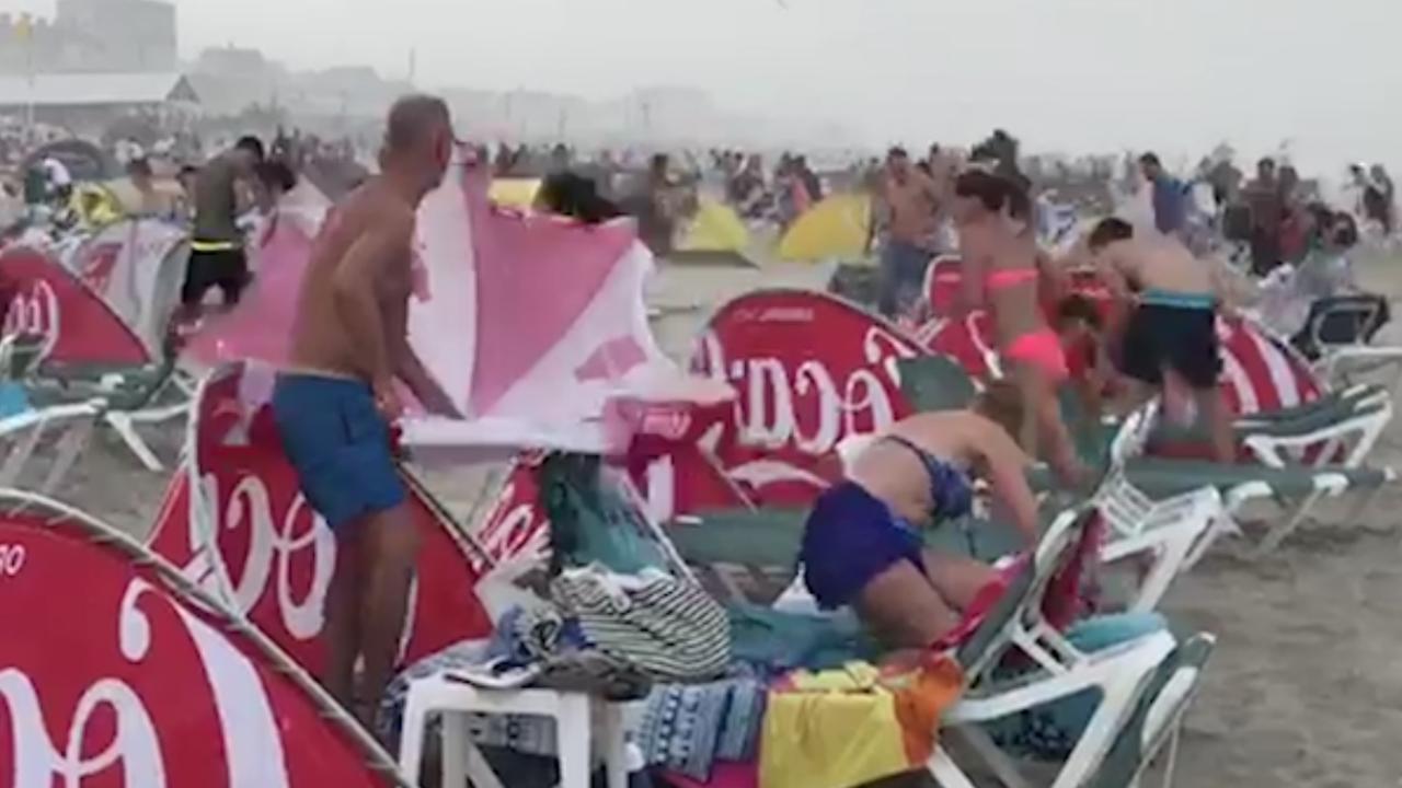 Badgasten vluchten van strand door enorme regenbui in Zandvoort