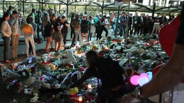 Mensen leggen zee van bloemen en knuffels bij spoorweg Oss
