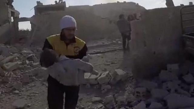Reddingswerkers halen kind onder ingestort gebouw in Syrië