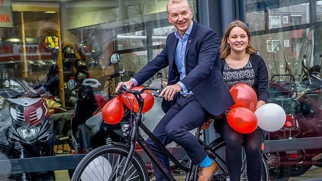 Wethouder Robert Strijk overhandigt nieuwe fiets aan 'flinke fietser'