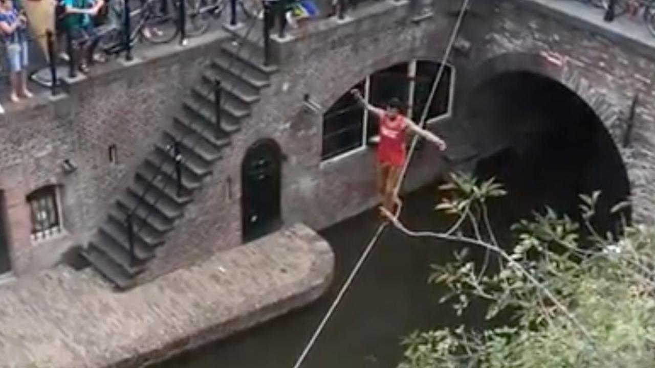 Koorddanser loopt over de Oudegracht in Utrecht