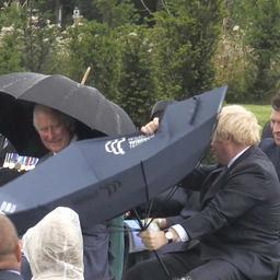 Video | Prins Charles lacht als Britse premier Johnson met paraplu worstelt