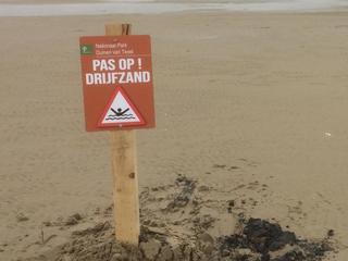 Meisje zakt tot haar middel weg in het zand op bouwterrein in Den Haag