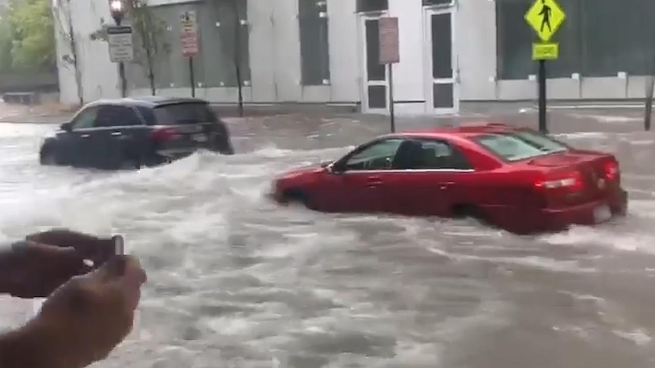 Auto's rijden door ondergelopen straten in VS na noodweer