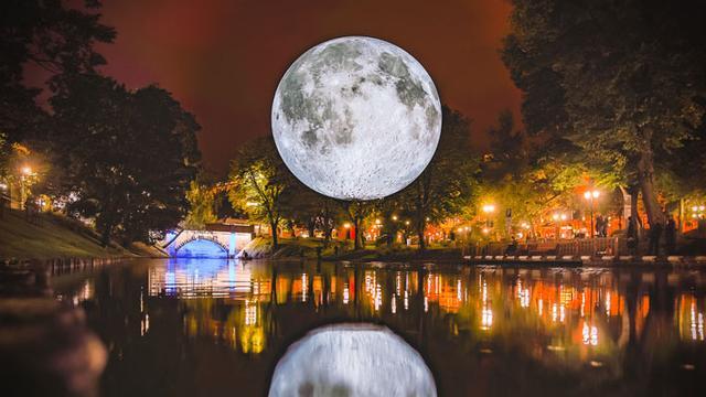 Levensecht schaalmodel van de maan verlicht het Waagplein