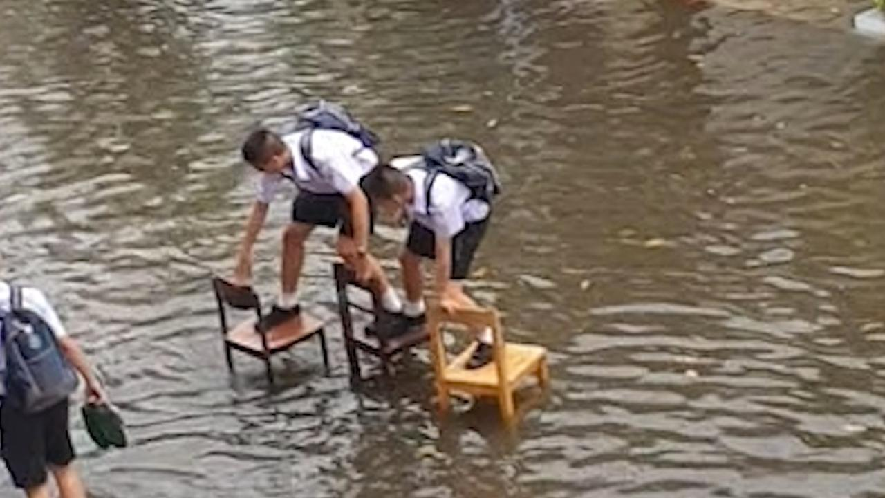 Thaise scholieren trotseren overstroming met stoelen