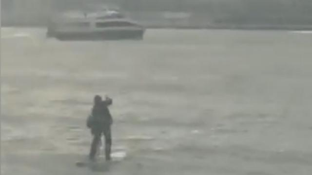 Man in pak steekt Hudson River over op paddleboard
