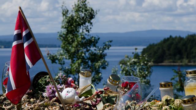 Bloemen en kaarsen met op de achtergrond de punt van het eiland Utøya bij Oslo.