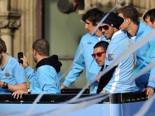 De spits van Manchester City toont tijdens het kampioensfeest een spandoek met de tekst 'RIP Fergie'.