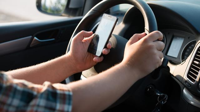 Rechter vindt bedienen smartphone in autohouder hetzelfde als vasthouden