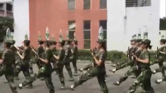 Chinese cadetten balanceren waterflessen op hoofd tijdens marcheren