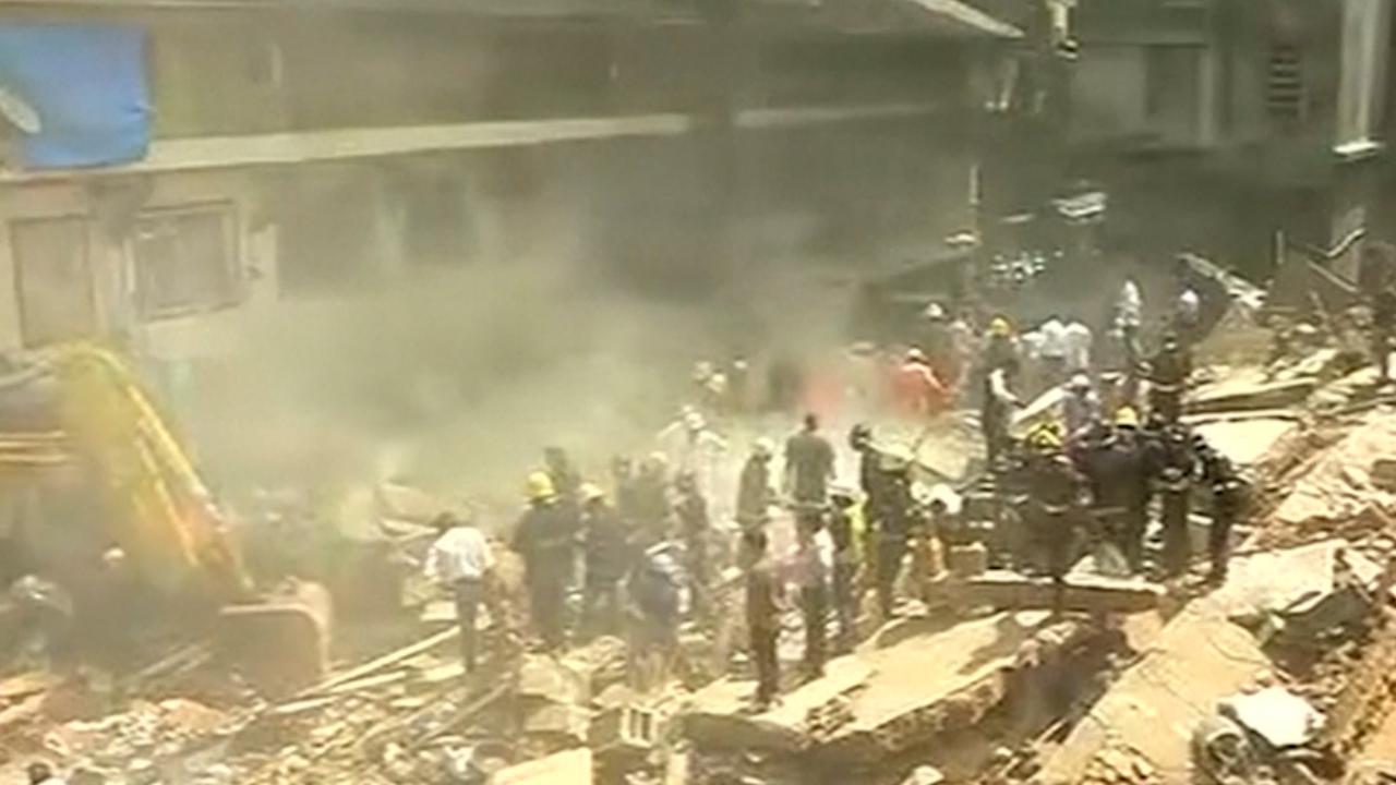 Omstanders halen mensen onder puin vandaan na instorten flat in Mumbai
