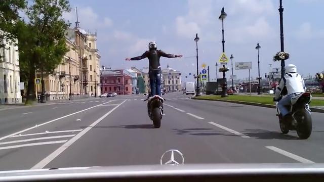 Stuntman gooit staand op motor confetti naar bruidspaar