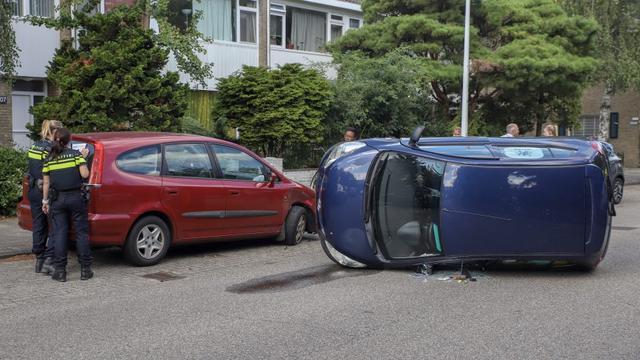 Auto op zijn kant na botsing tegen geparkeerde auto Gerard Brandtstraat