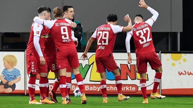 Spelers van Freiburg vieren feest na een goal tegen Dortmund.