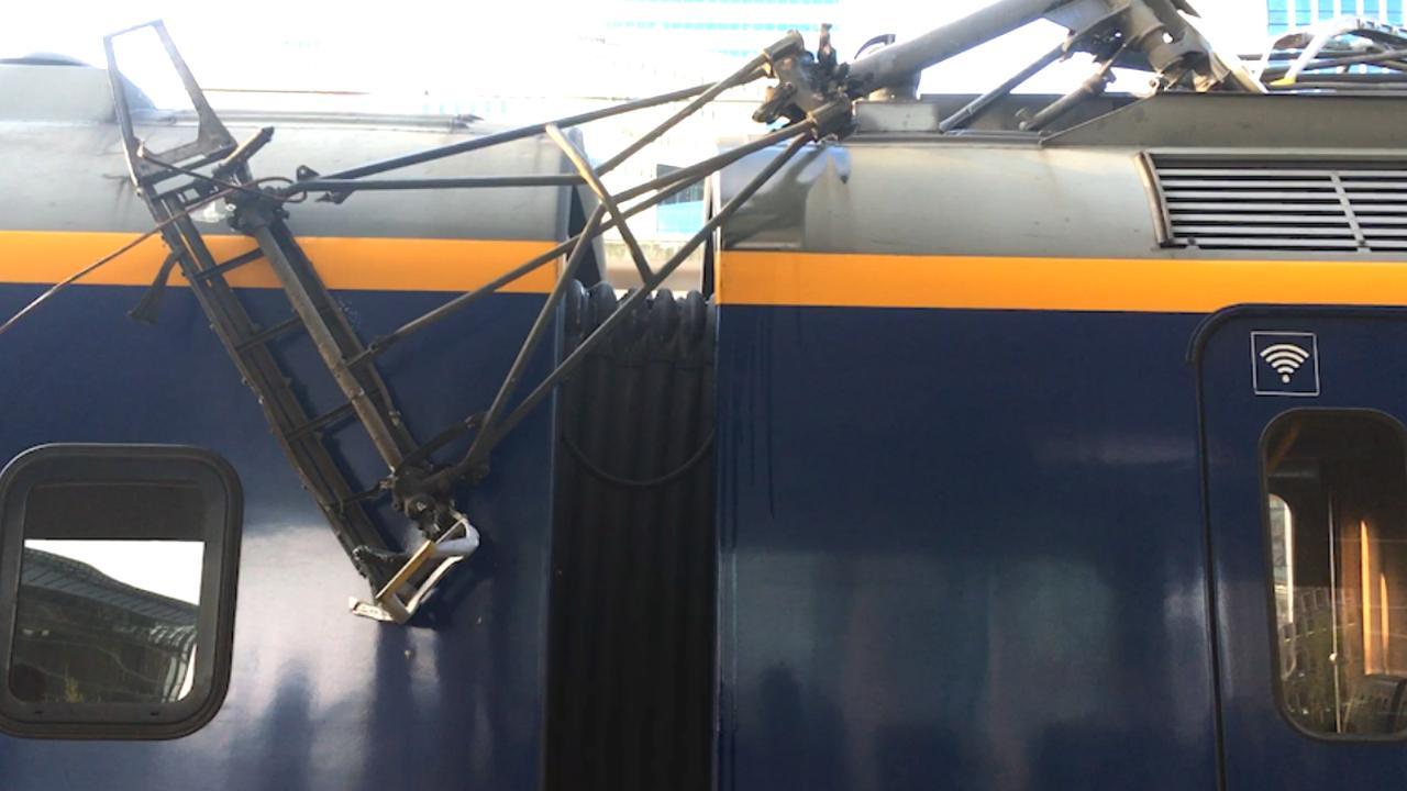 Pantograaf van NS-trein hangt los op station Amsterdam-Zuid