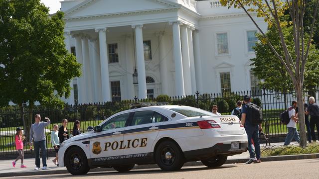 Man klimt met rugzak over hek Witte Huis
