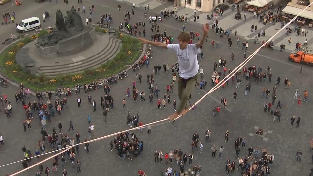 Koorddansers wandelen op zestig meter hoogte over plein Oude Stad Praag
