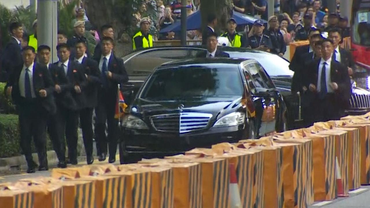 Bodyguards begeleiden auto Kim Jong-un in Singapore