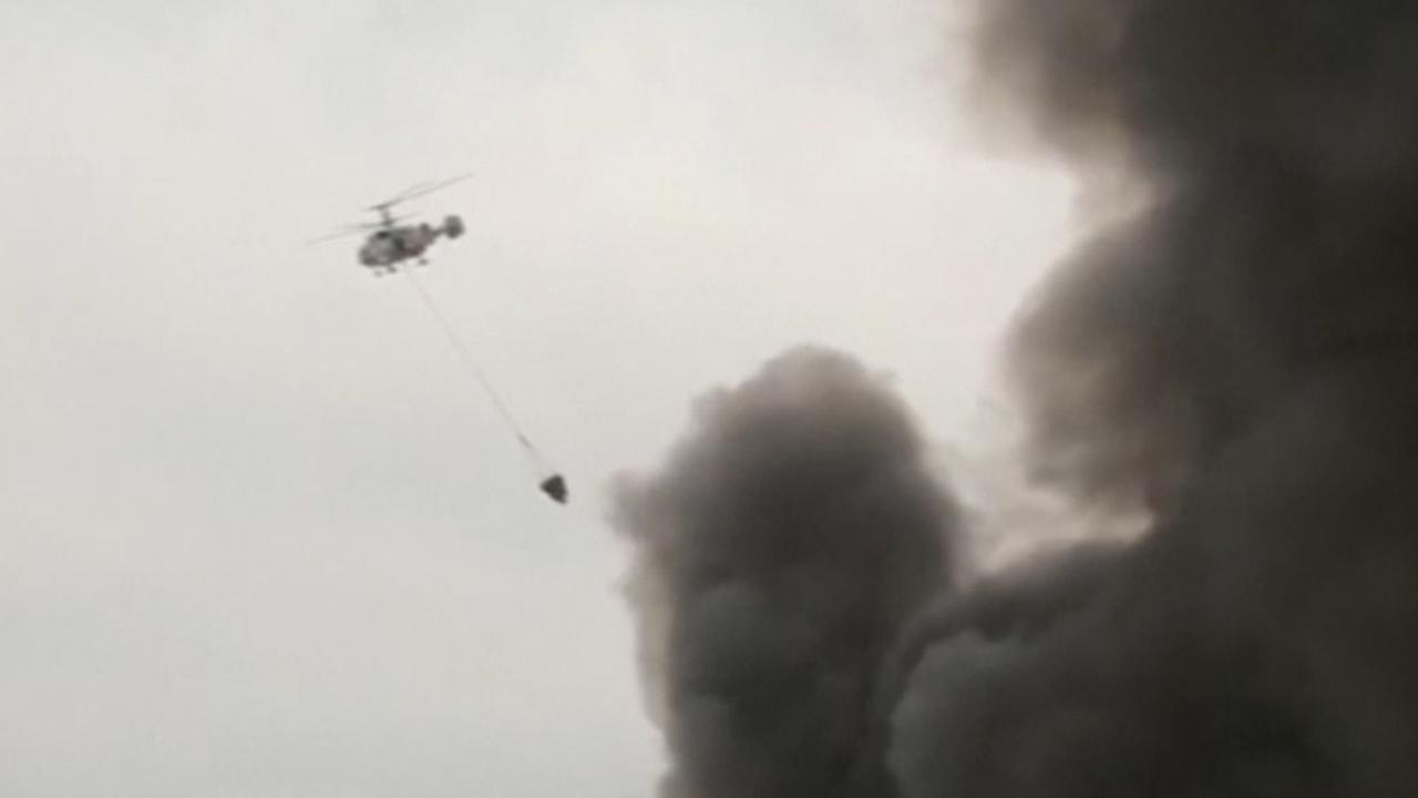 Blushelikopters lozen water boven grote brand in Moskou