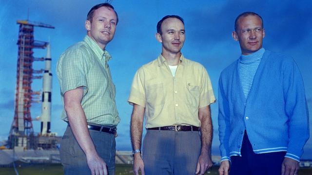 Michael Collins (midden), met links Neil Armstrong en rechts Buzz Aldrin. Op de achtergrond de Saturn V-raket van de Apollo 11-missie. (Foto: Getty)
