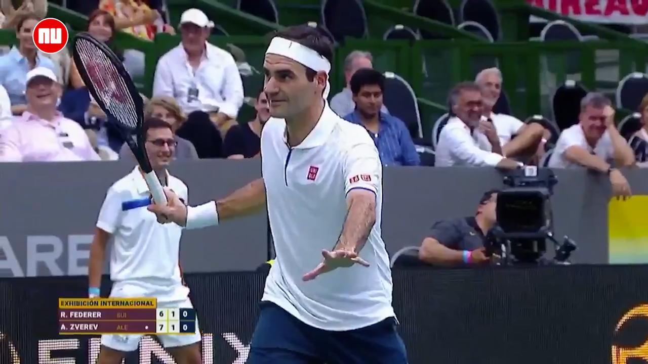 Roger Federer poseert halverwege demonstratiewedstrijd voor foto's