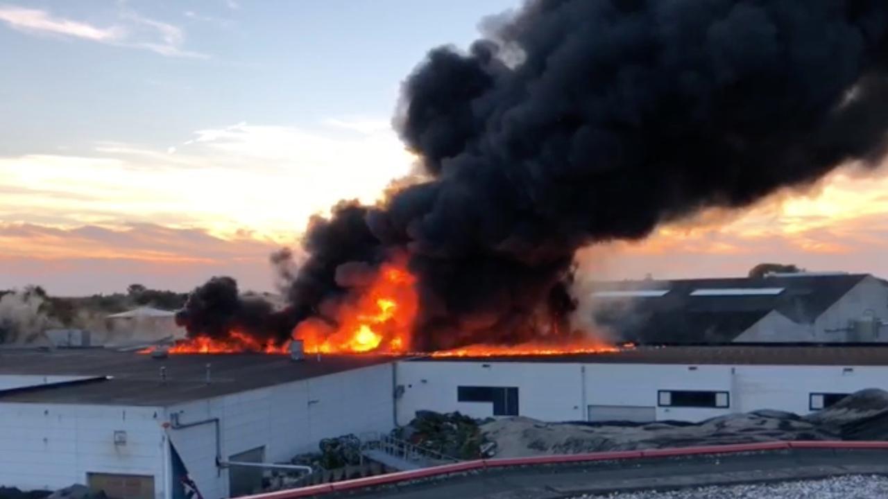 Vlammen slaan uit dak van recyclebedrijf in Dongen