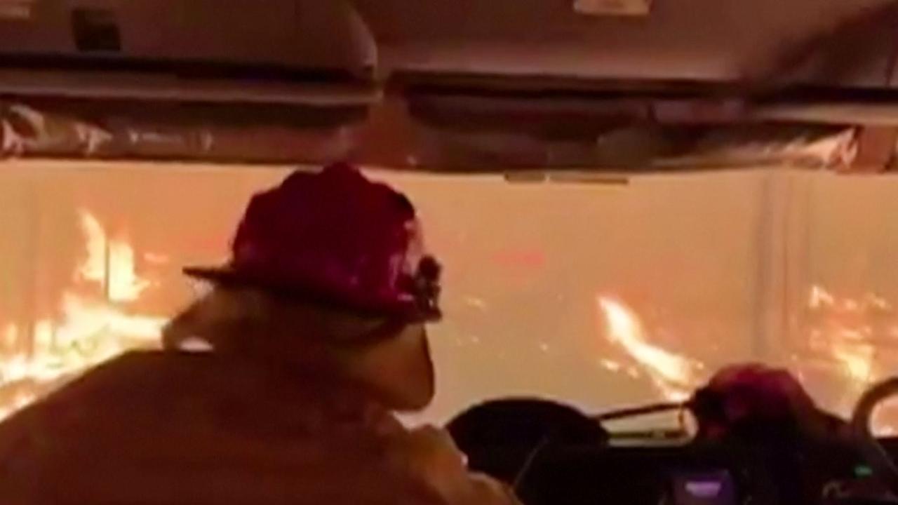 Australische brandweer rijdt dwars door bosbrand