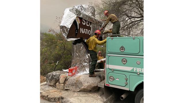 Brandweerlieden pakken een bord in met aluminiumfolie.