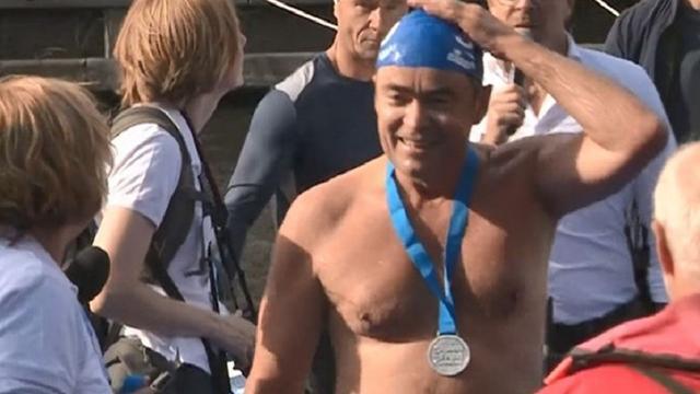 Burgemeester Haarlem zwemt City Swim onder politiebegeleiding