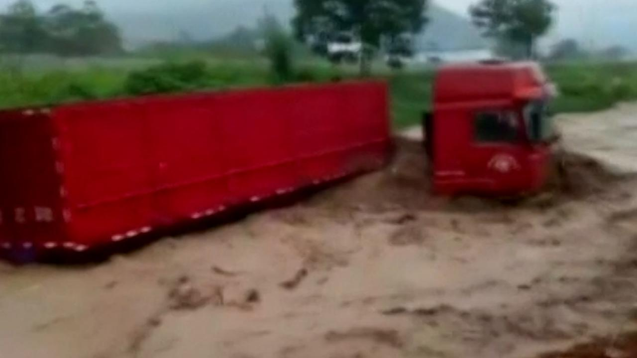 Overstroming sleurt vrachtwagen mee in China