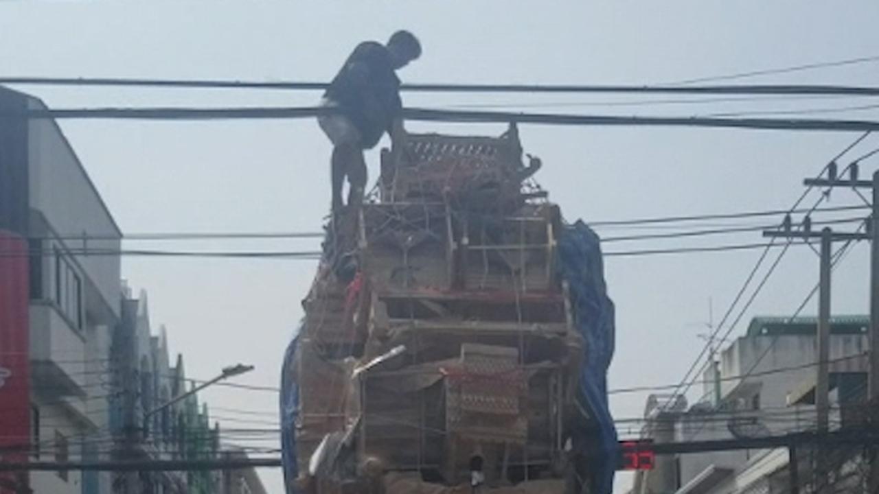 Man klimt op metershoge lading pick-uptruck Thailand