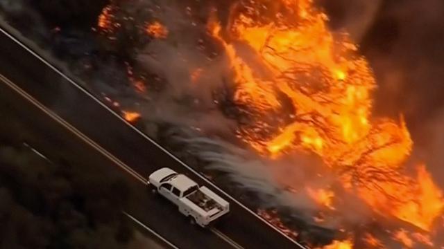 Auto rijdt rakelings langs natuurbrand bij snelweg Californië