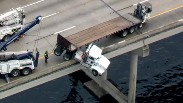 Vrachtwagen bungelt over brug in Florida