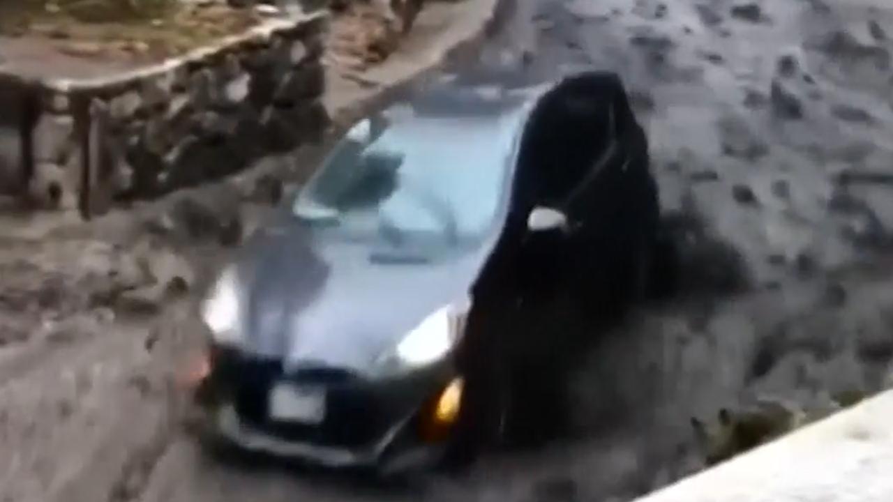 Auto glijdt mee met modderstroom in Californië