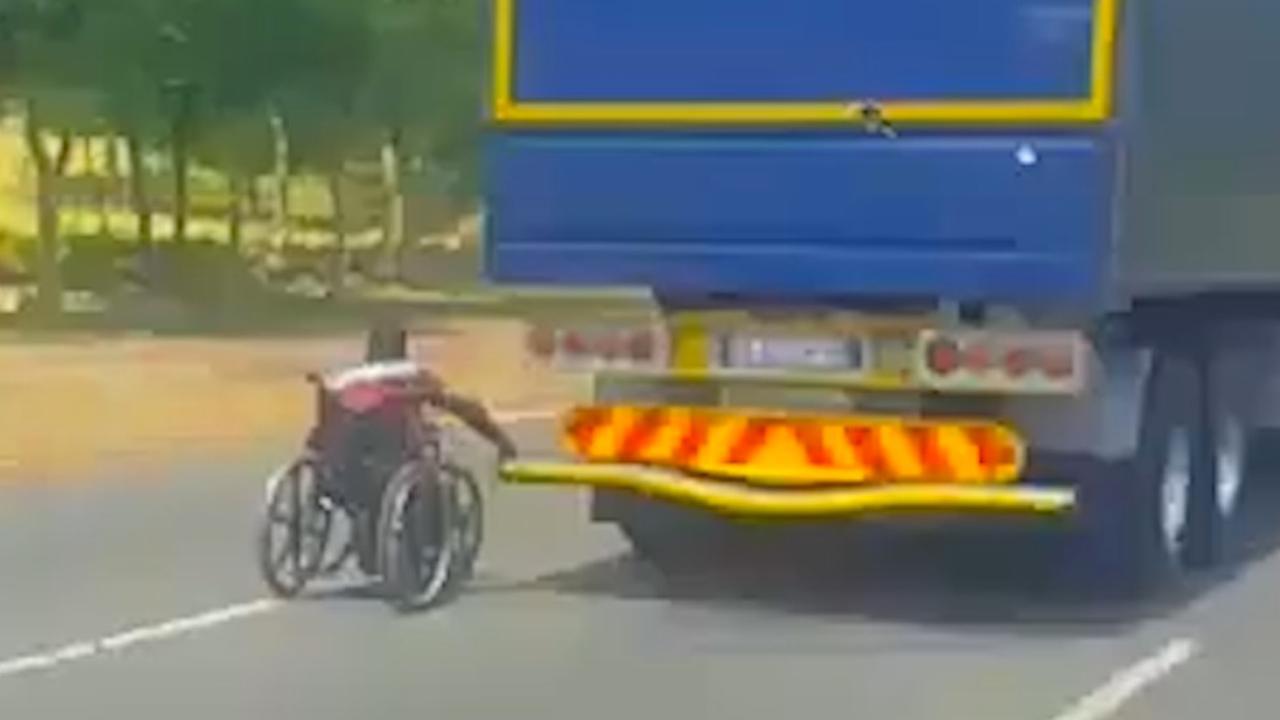 Rolstoelgebruiker Zuid-Afrika houdt zich vast aan vrachtwagen