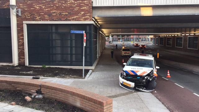 Politieauto zwaar beschadigd door botsing tegen muur