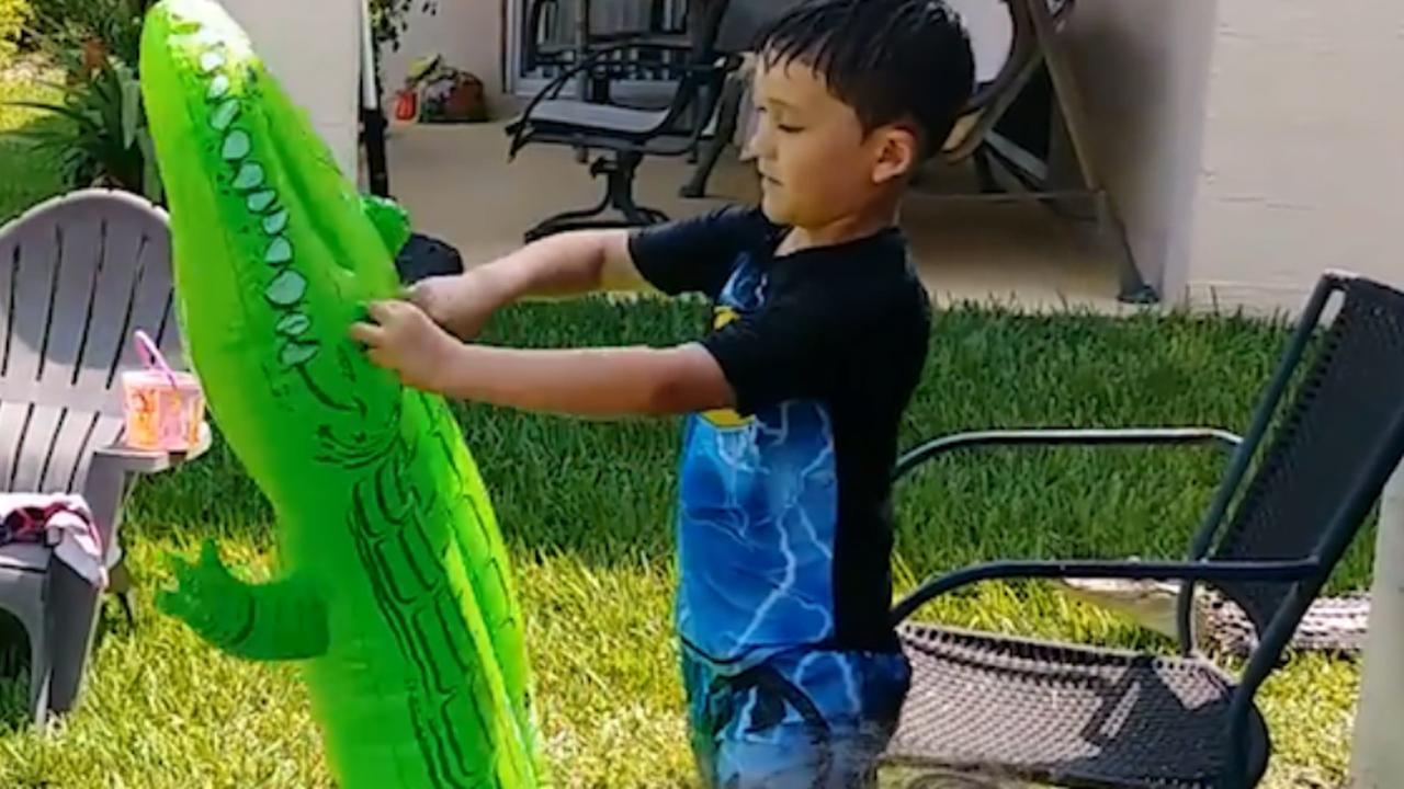 Alligator kijkt naar nietsvermoedend kind met opblaaskrokodil in VS